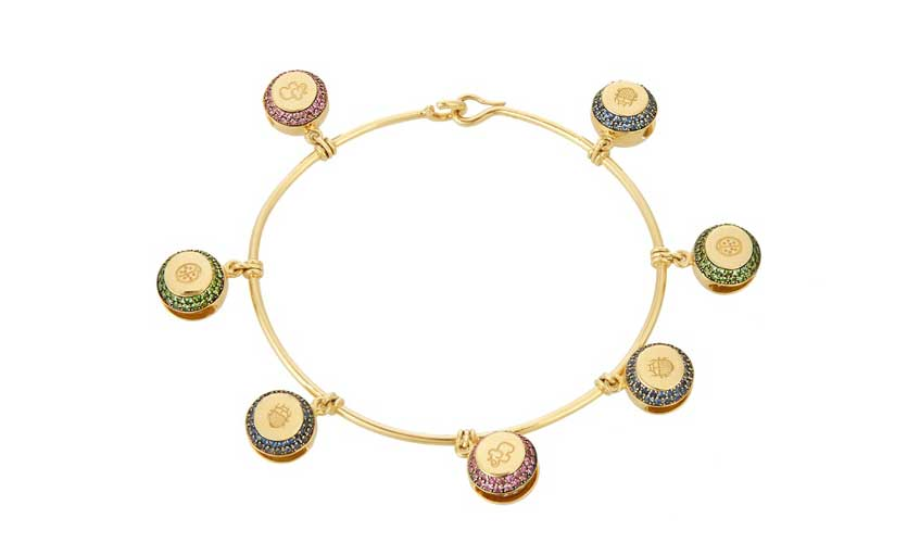 18k yellow-gold bracelet with bell charms, each engraved with a symbolic animal and studded with precious stones; blue sapphires, tsavorites, and amethyst, AURELIE BIDERMANN FINE JEWELLERY